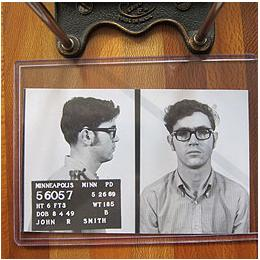 Black and white mugshot of man with glasses from the 1960's