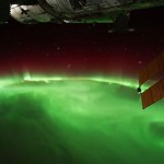 Earth from above showing green aurora and edge of the space station