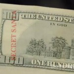 $100 USA bill with the words Secret Santa stamped on it