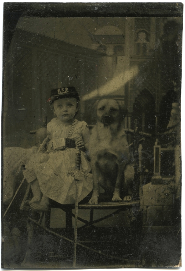old black and white photo of child with sword and military hat and dog