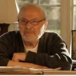 Maurice Sendak sitting at desk arms folded dark sweater glasses