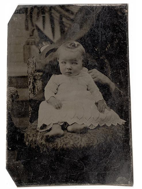 old black and white photo of baby in white dress held by a hidden mother