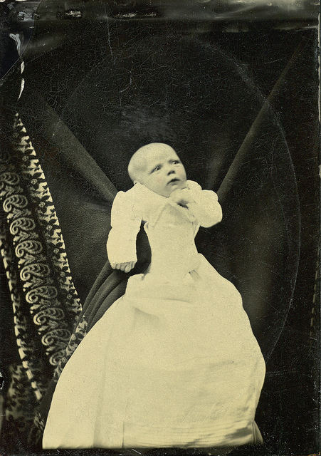 old black and white photo of baby in white in front of black background