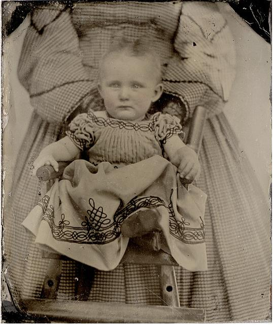old black and white photo of baby mother in background holding him face not visible