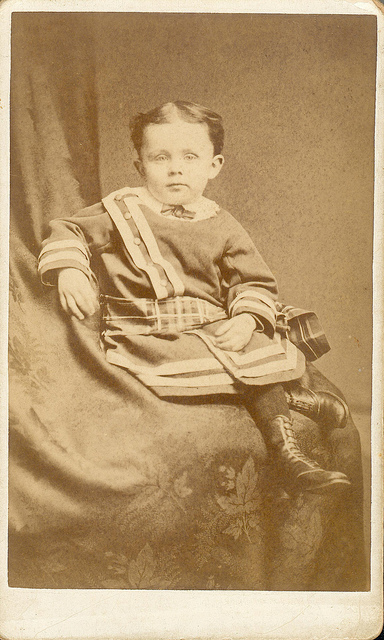 black and white sepia tone photo of small child with hidden mother