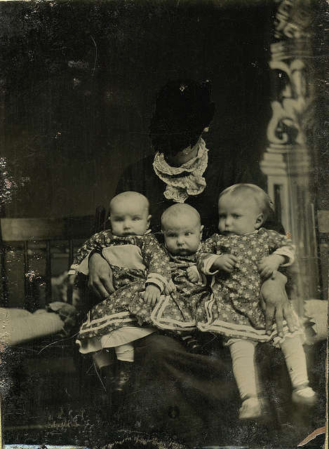 old black and white photo of triplets with hidden mother with face scratched out