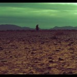dry parched earth in foreground greenish sky above