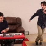 guy playing a red piano keyboard while another guy tap dances